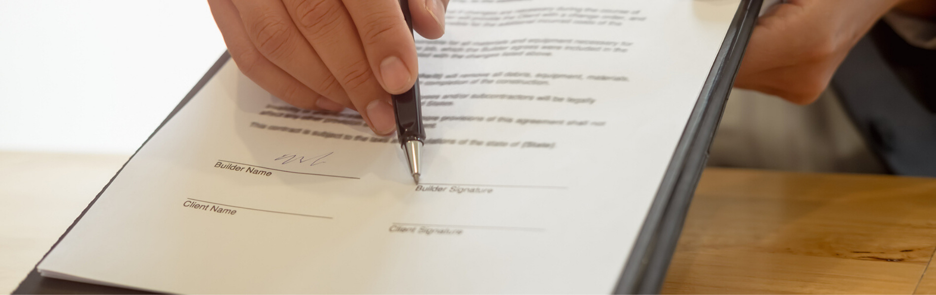 person holding a clipboard and pen for signature - Link to Contract Administration