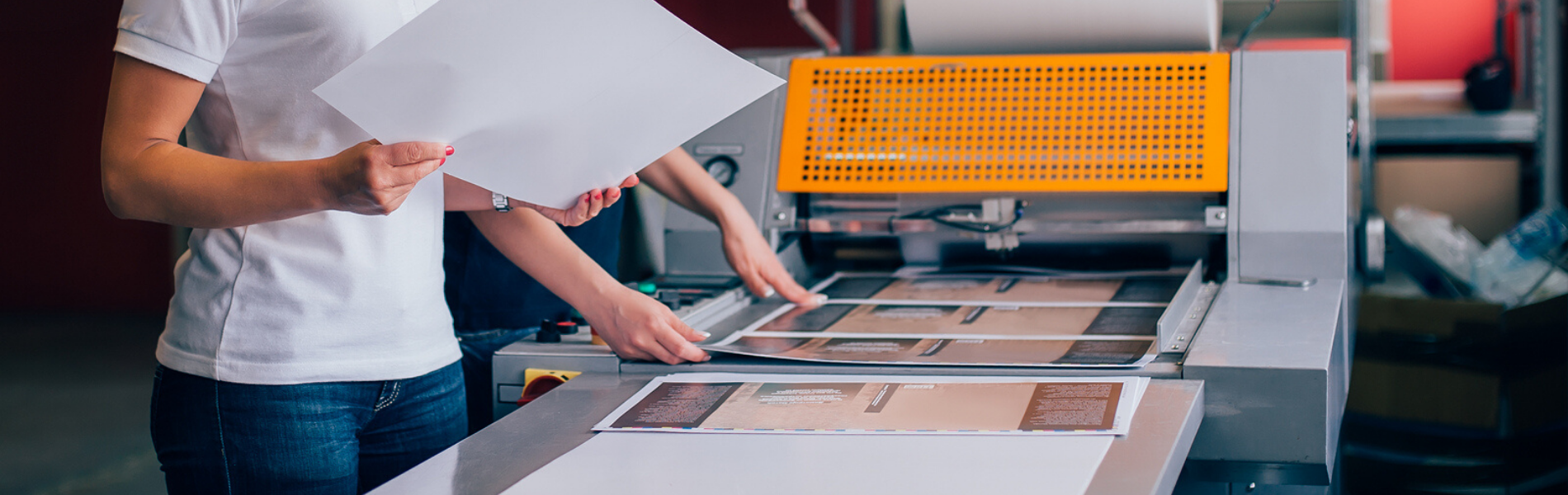 Close up of two people reviewing the output of a large format printer